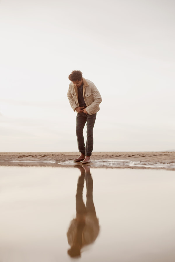 Portrait of young biracial man looking at his reflection by Anna Neubauer on 500px.com