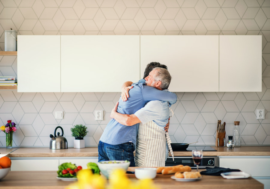 An adult hipster son and senior father indoors at home, hugging when cooking. by Jozef Polc on 500px.com